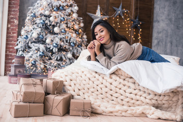 Happy Christmas morning in a home. Cold winter. Beautiful Asian girl in a sweeter and jeans laying on the white linens bad. Happy New Year's morning. Warmest Wishes For Christmas!