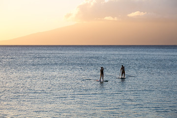 Silhouette of two standup paddlers on Maui, Hawaii
