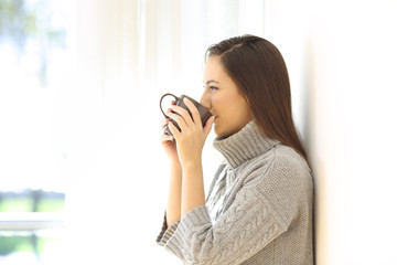 Woman drinking coffee looking through a window