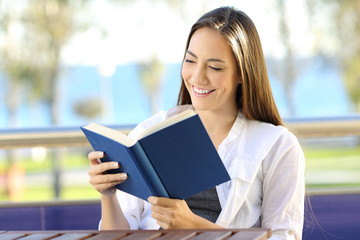 Woman reading a book during vacations on the beach