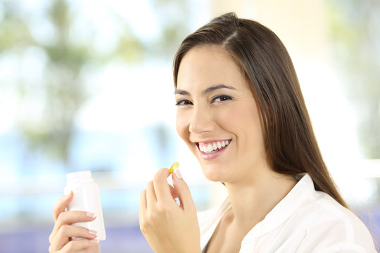 Happy woman holding a pill and bottle