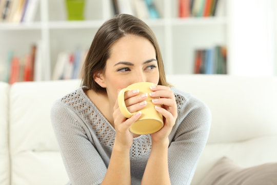 Woman drinking coffee looking at side at home