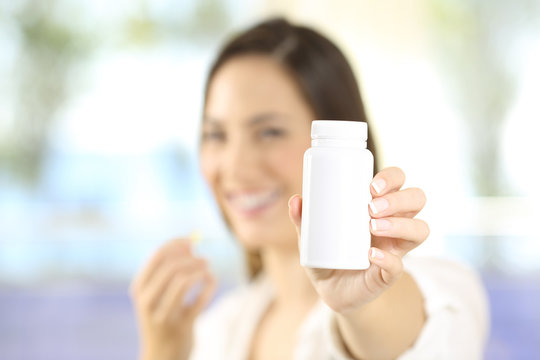 Woman showing a bottle of pills