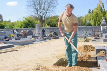 Man shovelling sand into grave