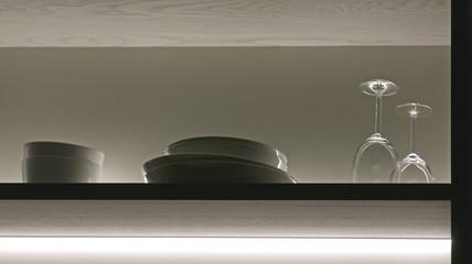 Weingläser, Teller und Schalen auf einem beleuchteten Regalbrett