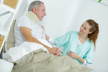 old man in bed with nurse touching his arm