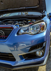 Engine component on show in a blue car with the hood popped