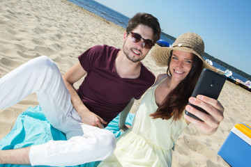 gorgeous young couple sitting at the beach and doing selfie