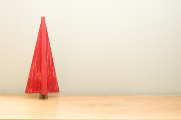 Wooden Red Christmas Tree on Wood Table against Pale Green Wall