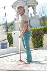 Maintenance man using rake in cemetery