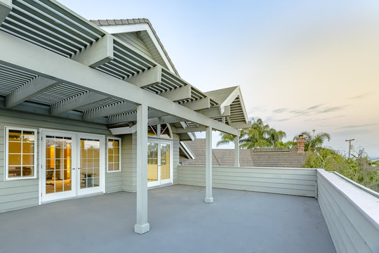 Large upstairs deck in southern California home with lattice covering at twilight