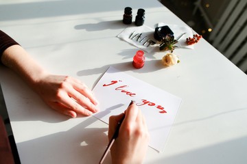 Hands of girl painter writes love text to postcard with with fou