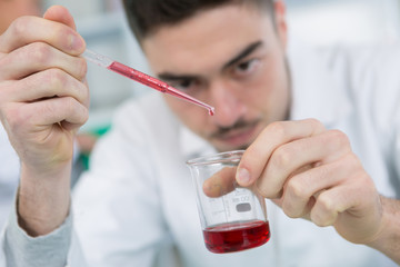 handsome male chemist setting up a blood test