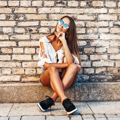 Fashion girl portrait in jeans shorts and sunglasses