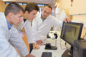 scientists looking at samples on screen through a microscope