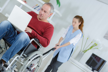 disabled man watching movie on laptop while cleaner is working