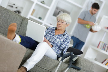 mature woman with injured leg relaxing on the sofa