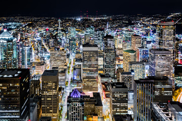 Fotomurales - Aerial view of Seattle downtown skyline at night, with modern skyscrapers and bright city lights