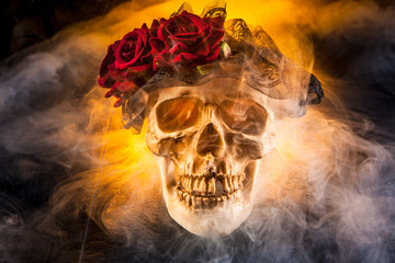 The skull of a man in the smoke. Skull with a wreath of flowers.