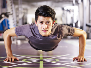 young asian man doing push-ups in gym
