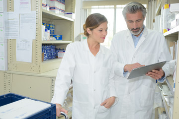 efficient male and female pharmacists in drug store