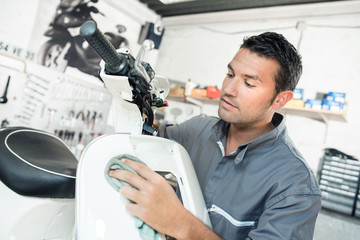 man polishing scooter