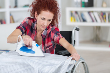 pretty redhead woman sitting on wheelchair and ironing