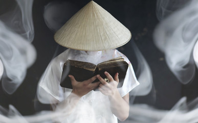 Asian man in a kimono prays with a book