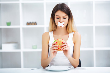 Diet. Young beautiful woman eating burger, It's junk and unhealthy food, Beauty face natural makeup