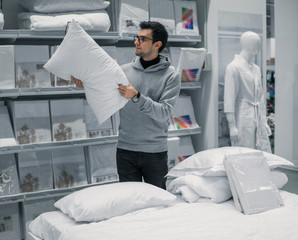 Customer man chooses bed linen and bed in the supermarket mall store. He is j examining one pillow.