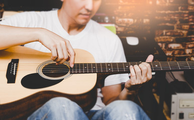 asian man playing acoustic guitar, focus on hands