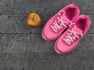 Pink running shoes for fitness classes at the gym and a ripe Apple on a wooden floor.
