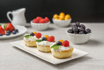 Mini cheesecakes with Strawberry and whipped cream on a plate.