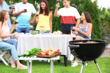 Barbecue grill, table with prepared vegetables and blurred people on background