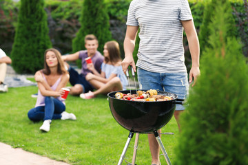 Man cooking tasty steaks on barbecue grill for party, outdoors