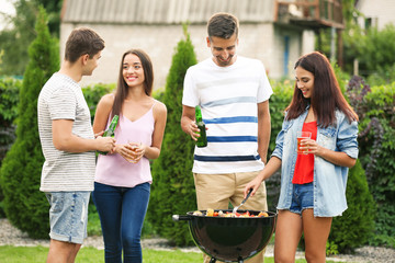 Young friends having barbecue party in garden