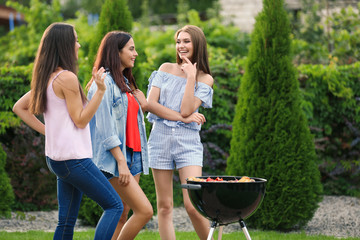 Women cooking tasty food on barbecue grill, outdoors