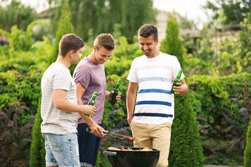 Men cooking tasty food on barbecue grill, outdoors
