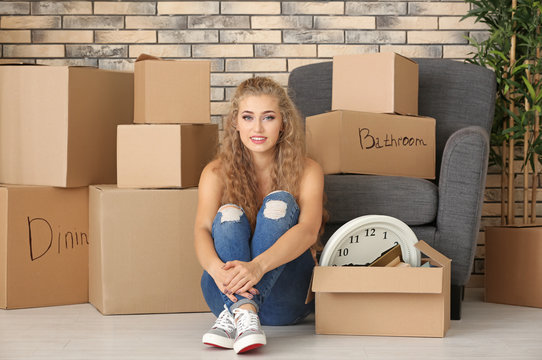 Young woman sitting on floor and moving boxes in room