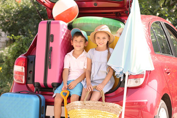 Cute children near car with things prepared for rest at sea resort