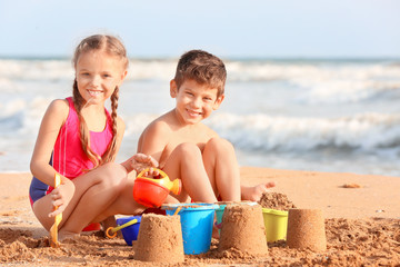 Cute children playing with sand on sea beach