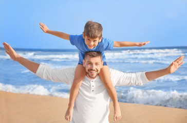 Cute little boy with father on sea beach at resort