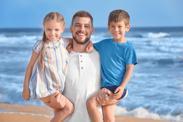 Cute little children with father on sea beach at resort