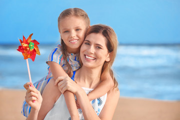 Cute little girl with mother on sea beach at resort