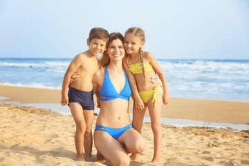 Cute little children with mother on sea beach at resort
