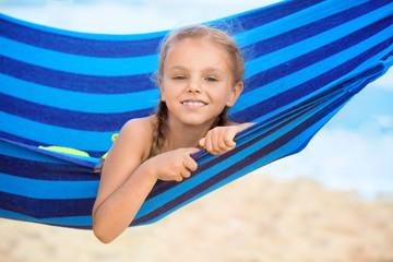 Cute little girl lying in hammock on sea beach at resort