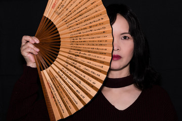 A close up portrait of an oriental woman, half face covered by a fan,  on a black background