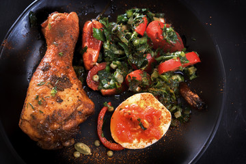 Fried chicken leg in a black plate with a tomato salad, egg and sauce. Mediterranean cuisine.  view from above