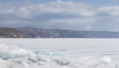 Transparent blue ice hummocks on lake Baikal shore. Siberia winter landscape view. Snow-covered ice of the lake. Big cracks in the ice floe.