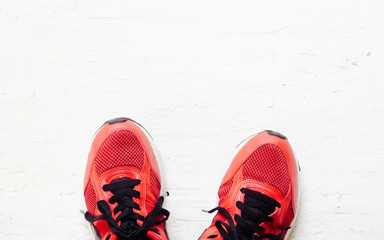 Pair of red sport shoes laid on grunge white wooden floor background, top view with copy space